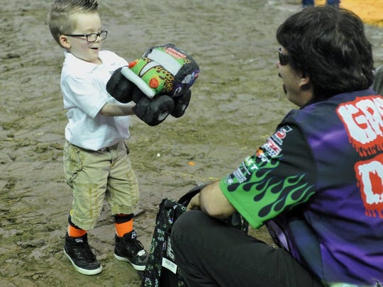 JASON CLARK / COURIER & PRESS Braxton Wiley, 4, clutches onto his new Grave Digger plush monster truck after receiving it from Grave Digger driver Charlie Pauken before the start of Monster Jam at the Ford Center in Evansville last year. Wiley was treated to a special meet and greet with drivers thanks to the help of Wish Upon a Star and Monster Jam.
