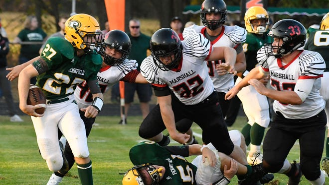 Pennfield RB Ian Messenger (27) rushes for positive yards as a Redhawk defender trips over a Panther lineman.