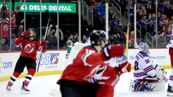 New Jersey Devils center Blake Coleman, left, celebrates after scoring a goal on New York Rangers goalie Henrik Lundqvist, right, of Sweden, during the second period of an NHL hockey game Thursday, Dec. 21, 2017, in Newark, N.J. (AP Photo/Julio Cortez)