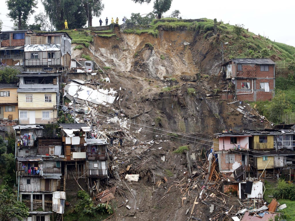 Rescue workers survey an area where a landslide destroyed several homes in Manizales, Caldas, Colombia. At least 11 people were killed and 20 are missing after heavy rains caused landslides in this mountainous region of Colombia.