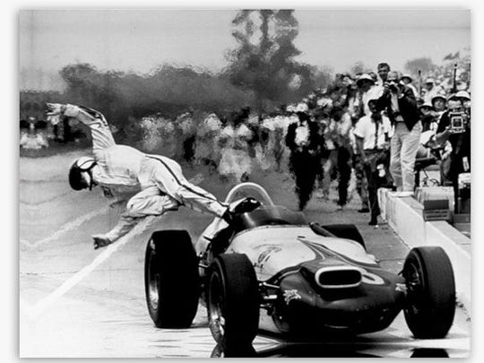 Parnelli Jones leaps from his race car after it caught fire during a pit stop in the 1964 Indy 500. Jones was not hurt.