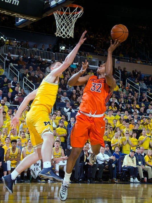 Virginia Tech forward Zach LeDay (32) attempts a shot as Michigan center Jon Teske, left, defends during the first half of an NCAA college basketball game at Crisler Center in Ann Arbor, Mich., Wednesday, Nov. 30, 2016. (AP Photo/Tony Ding)