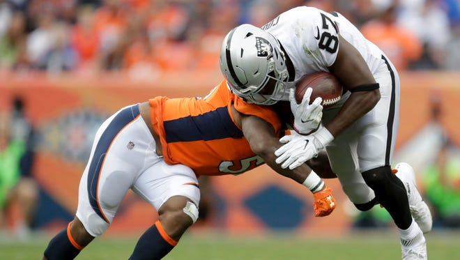 Oakland Raiders tight end Jared Cook, right, is tackled by Denver Broncos inside linebacker Todd Davis during the second half of an NFL football game Sunday, Oct. 1, 2017, in Denver.