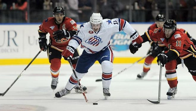 Amerks center Tim Schaller sprints away from Flames defenders in Friday's 6-1 opening-night victory.