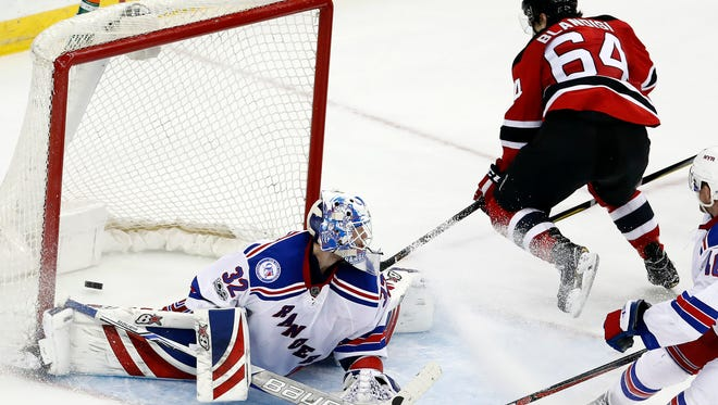 New Jersey Devils left wing Joseph Blandisi (64) scores the game-winning goal on New York Rangers goalie Antti Raanta (32), of Finland, during the overtime of an NHL hockey game, Tuesday, March 21, 2017, in Newark, N.J. The Devils won 3-2. (AP Photo/Julio Cortez)