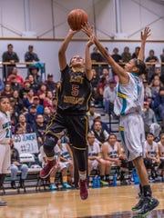 Tohatchi's Kalian Mitchell scores over Navajo Prep's Martinique Larvingo on Thursday at the Eagles Nest.