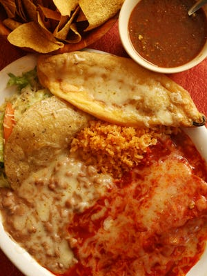 A combination plate with red sauce from Chope's includes an enchilada, taco, chile relleno, and rice and beans, and comes with chips and salsa.