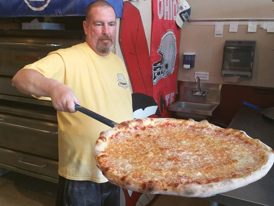 Glenn Beekman pulls a massive pizza from the oven at Pizza D-LUX in south Fort Myers.