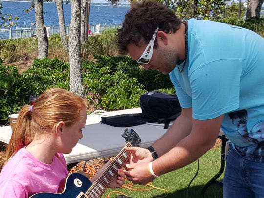 Ian Waldron shows a girl how to play guitar during