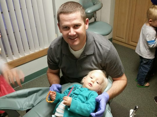 Dr. Cody Hughes works on his 18-month-old daughter Kate.
