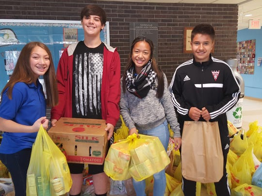Some food drive helpers transporting goods to the truck. Left to right: Zoe Iwaniak, Christopher Smith, Eliza David, Dylan Rodriguez.