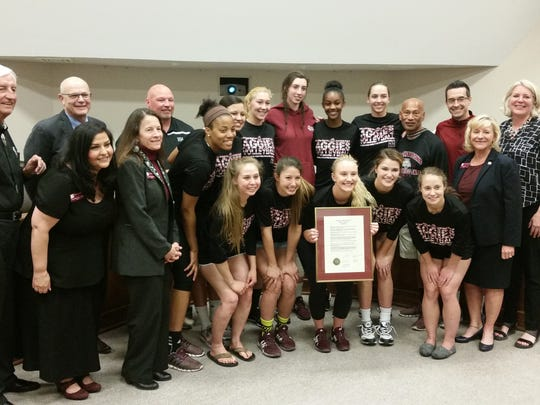 President Garrey Carruthers and NMSU regents pose with members of the NMSU volleyball team at the April 4 meeting of the board of regents. The team was recognized with a resolution for winning a conference championship, along with the women's basketball team, the men's basketball team and the equestrian team.