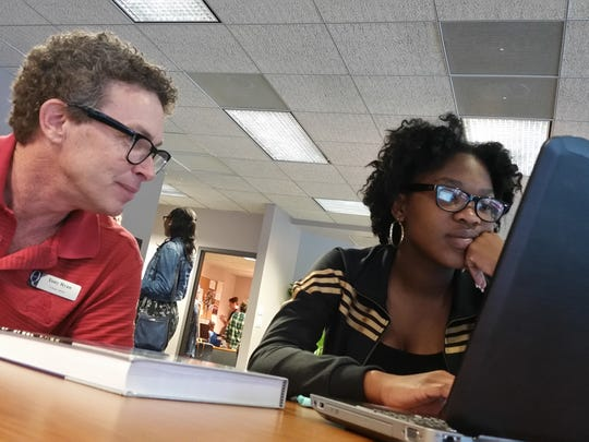 Tony Ryan,(left)  a college adviser at Quest for Success, helps high school student Kesline Senesca, 17, with precalculus. Quest is a Naples-based organization that prepares students for college and encourages them to graduate in four years.