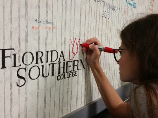 It is a tradition for high school seniors to write the names of the colleges where they plan to attend on the walls at Quest for Success, a Naples college preparatory organization. Olivia Cona, 18, plans to attend Florida Southern College in the fall.