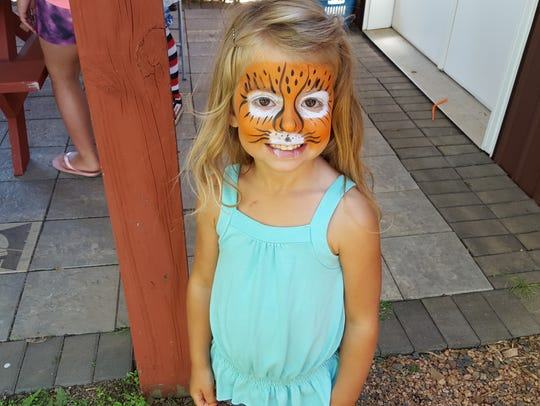 A child poses after having her face painted at Music