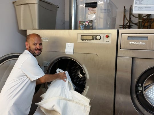 Wilfredy Betancur, an employee of Linder's French Cleaners in Bernardsville, loads one of the Bernardsville's dry cleaner's cool-water washing machines. The firm has looked for new revenue opportunities because people are bringing fewer items for dry cleaning.
