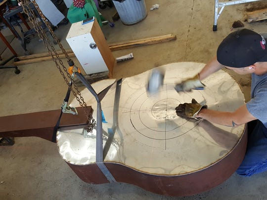 Putnam Township artist Steve Cannaert hammers the shape of the resonator on the Dobro, an instrument he will enter in the 2016 ArtPrize competition in Grand Rapids.