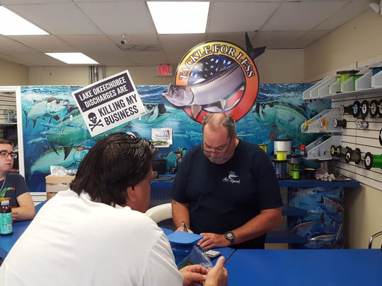 Tim Kenney, right, owner of Tackle For Less in Stuart, rings up Bruce Hrobak, center, owner of Billy Bones Bait and Tackle stores in Port St. Lucie and Stuart, as Tanner Hrobak, left, looks on. Kenney is closing his business after two years due to Lake Okeechobee discharges.