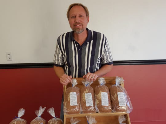 Gary Burich poses next to some bread he brought to