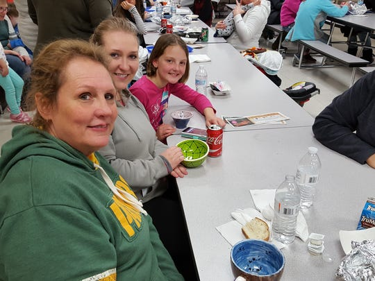 Wanda McCarthy, Colleen Richter and Madeline Mudler, 8, show off their bowls as Shannon Mudler looks on Saturday at the Empty Bowls event at Wausau West on Saturday.
