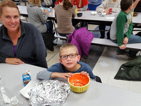 Shannon Mudler smiles as her son Gunner, 6, shows off his empty bowl.