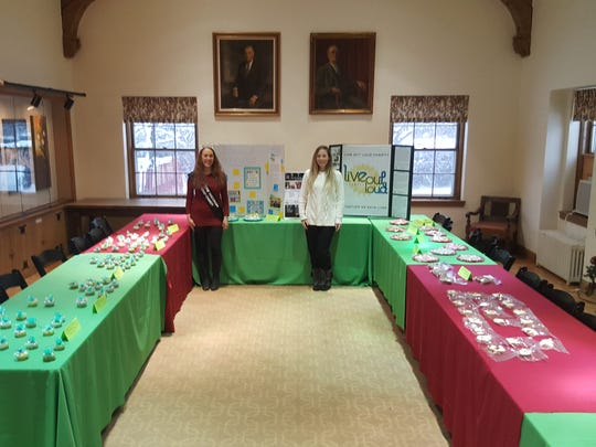 Live Out Loud founder Sherrie Gearheart, right, and Mrs. Worldwide Wisconsin Ambassador Nancy Steinle, left, stand among the baked goods set up for sale while snow falls outside.