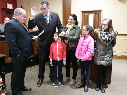 Pompton Lakes Mayor Michael Serra administers Oath of Office to Christian Barranco who is surrounded by his family.