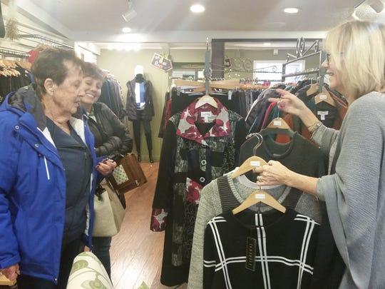 Customers talk to Karen Alexander about merchandise.