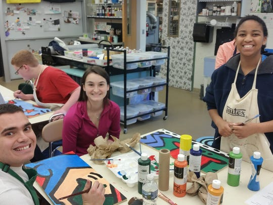 Seneca High School students Jason Magepinto (left), Susie Foley (middle) and Sunday Kessinger work on the mural.