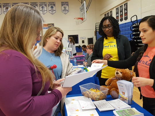 Members of the public receive information from Kind to Kids before the start of an Imagine Delaware forum on child abuse prevention at Cab Calloway School of the Arts in Wilmington on Friday.