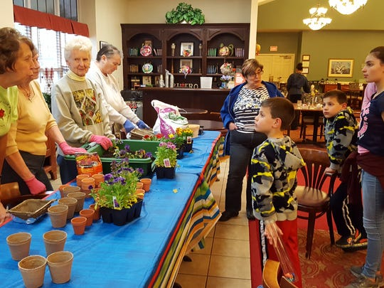 On April 22, Neshanic Garden Club members were involved at Earth Day celebrations at Brookdale Hillsborough, a senior living community. Club members potted spring plants for the residents and their visitors. A local Boy Scout was putting in a bocce ball court to earn his Eagle Scout badge, and a magician/ventriloquist entertained the residents and guests. From left: club members Diana Reinhardt, Marion Nation, Jean Stives and Barbara Majewski speak with some of the guests at Brookdale's Earth Day.