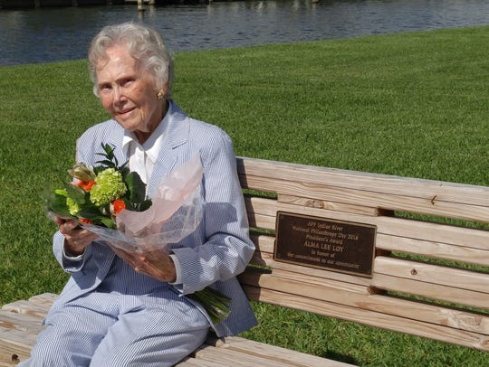 Alma Lee Loy sits on the bench that includes a plaque,