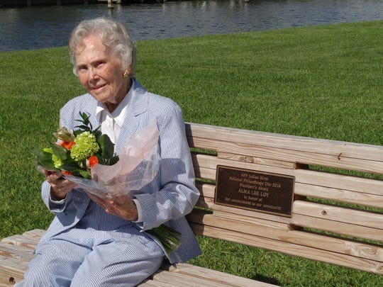 Alma Lee Loy sits on the bench that includes a plaque, dedicating the bench in her name