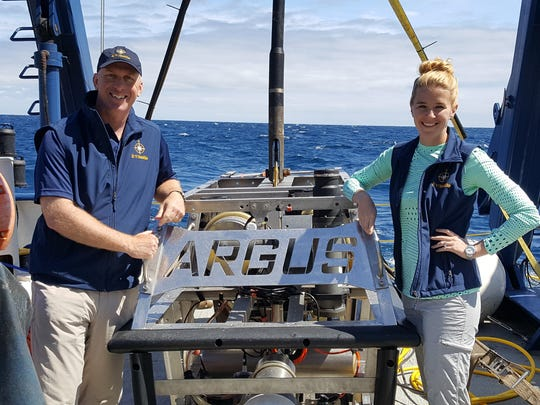 Jon Willis (left) and Kaitlyn Lowen, both science communication fellows, pose with the remote-operated vehicle Argus, which is piloted from a command center aboard the Exploration Vessel Nautilus.