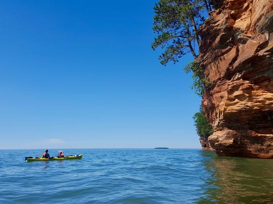Sea kayakers admire the mainland sea caves of the Apostle