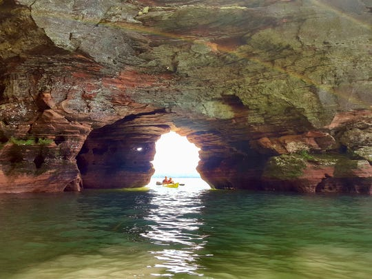 Kayakers paddle through a tunnel in the mainland sea