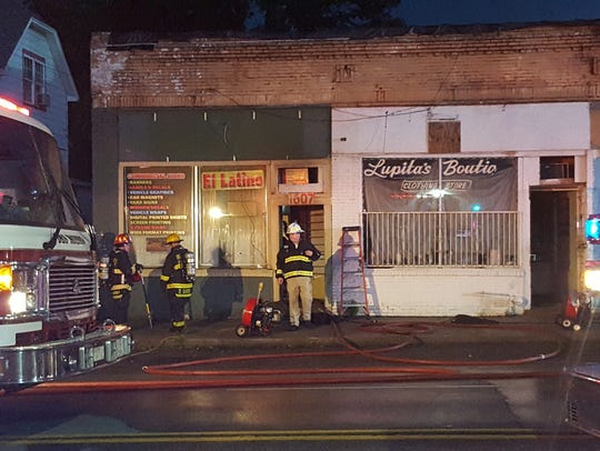 Firefighters emerge from the damaged building on Monday,
