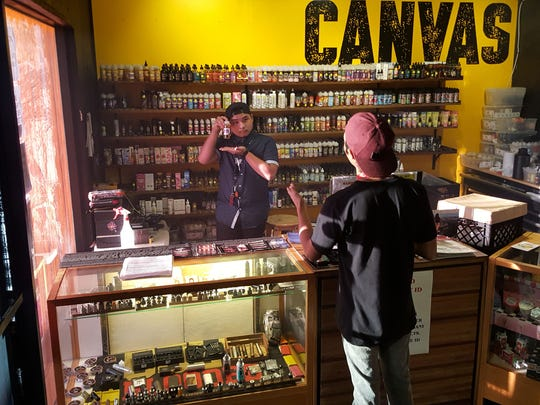 A Canvas employee shows customers a bottle of vape juice from the shop's wide selection.