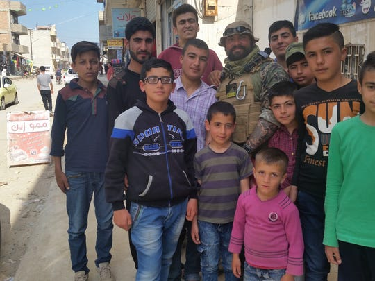 Anthony Delgatto, a bouncer from Sea Bright, poses with children in the streets of Syria. He joined up with a Kurdish militia to fight ISIS in Syria.