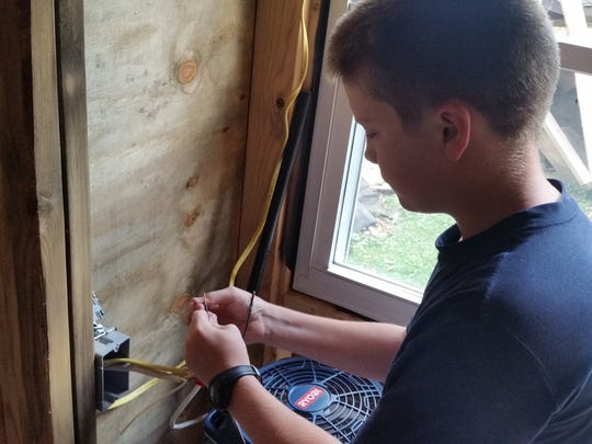Luke Thill of Dubuque, with guidance from a neighbor, learned to do some of his own wiring on the tiny home he built.