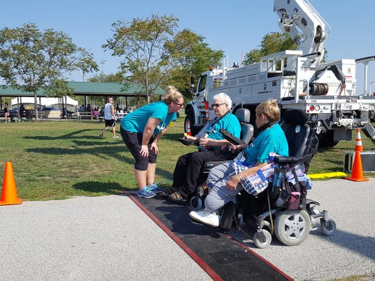 Event director Anna Fuller speaks with two participants as they cross the finish line at the Eighth Annual Iowa Remembrance Run on Sunday, September 24, 2017.