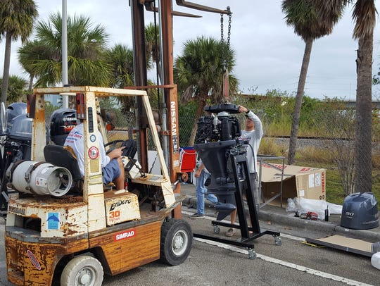 The crew from Central Marine in Stuart lift a display