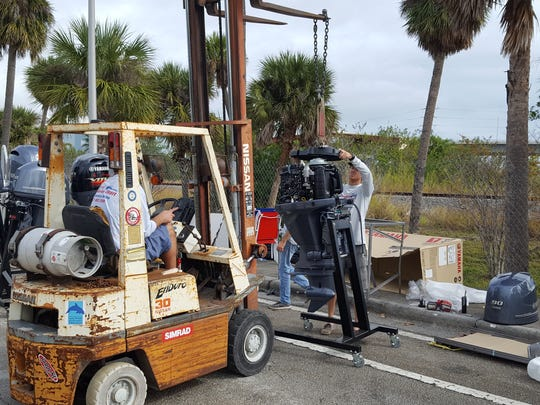 The crew from Central Marine in Stuart lift a display Yamaha Outboard motor onto a motor stand for display at this weekend's Stuart Boat Show open Friday through Sunday.
