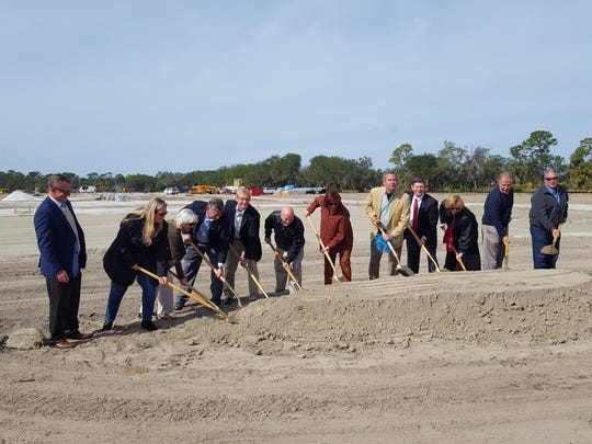 Scott Deal (tan coat, center), CEO of Maverick Boat Group in Fort Pierce, and members of the Economic Development Council of St. Lucie County and other officials celebrate the groundbreaking of a 106,000 square foot facility to build Cobia boats in Fort Pierce.