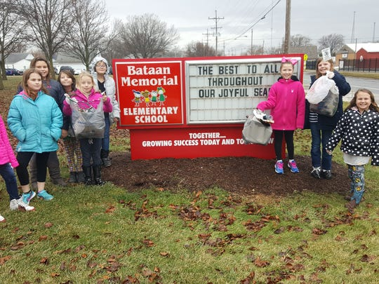 A Bataan Memorial Elementary School's past Clean Up Club stand next to the school sign. Students are preparing to return to classes in coming weeks and the district will be holding open house events for all its buildings.