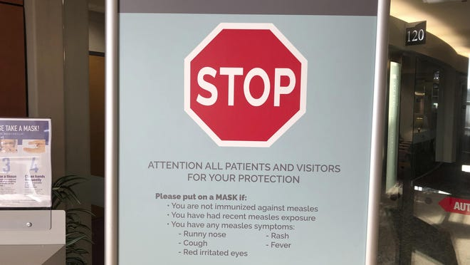 In this Jan. 30, 2019, photo, signs posted at the Vancouver Clinic in Vancouver, Washington, warn patients and visitors of a measles outbreak.