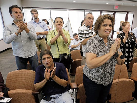 Members of various organizations applaud after City Council passed an anti-wage theft ordinance on Tuesday.