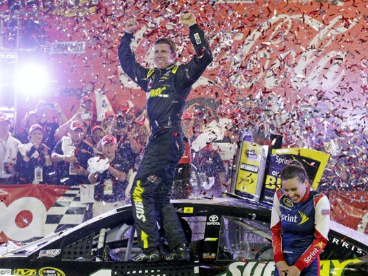 Carl Edwards celebrates in victory lane after winning Sunday's NASCAR Sprint Cup race at Charlotte Motor Speedway in Concord, N.C.