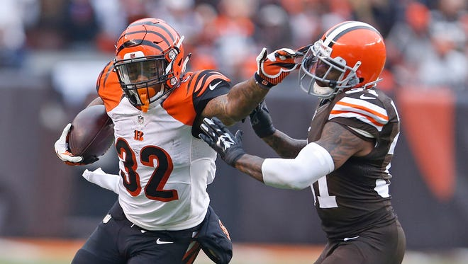 Bengals running back Jeremy Hill stiff-arms Browns strong safety Donte Whitner during the second quarter Sunday.