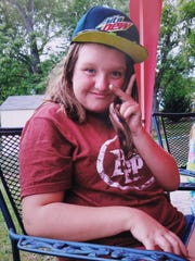 In this 2015 photo provided by Tammy Weeks, her daughter, Nicole Lovell, flashes a peace sign in Blacksburg, Va.